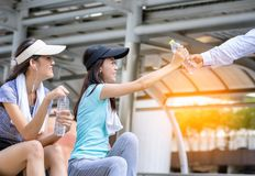 Man hand offer a bottle of water to young sport woman after wor. Man hand offer a bottle of water to young sport women after work out Stock Photo