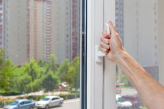 Man Hand opens a plastic pvc window. Royalty Free Stock Photography