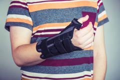 Man with hand in orthopedic black orthosis. Man with hand orthopedic orthosis - studio image royalty free stock images