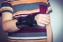 Man with hand in orthopedic black orthosis. Man with hand orthopedic orthosis - studio image royalty free stock photo