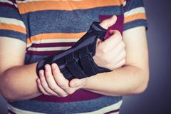 Man with hand in orthopedic black orthosis. Man with hand orthopedic orthosis - studio image stock photos
