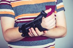 Man with hand in orthopedic black orthosis. Man with hand orthopedic orthosis - studio image royalty free stock photos