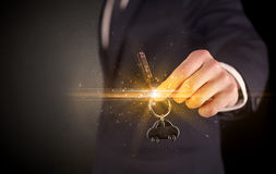 Man hand over keys. Businessman hand  over shiny keys in dark suit with dark background Stock Photos