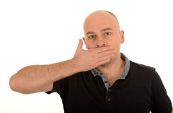 Man with hand over mouth. Bald middle aged man with hand over mouth, speak no evil concept isolated on white background Stock Photos