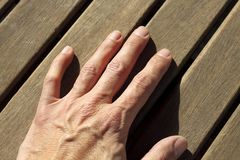 Man hand over sunny teak wood lines Stock Images