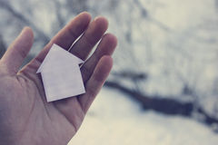 Man hand paper home. Background of snow Stock Image