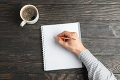 Man hand with pen, copybook and cup of coffee royalty free stock images
