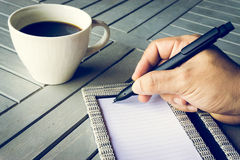 Man hand with pen writing on notebook. Coffee and notebook on wooden table. Royalty Free Stock Images