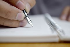 Man hand with pen writing on notebook. Closeup Stock Photography