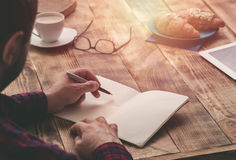 Man hand with pen writing on notebook on wooden table Royalty Free Stock Photo