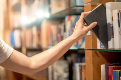 Man hand picking a book from bookshelf Stock Images