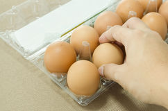 Man hand picking eggs from package. Man hand picking organic egg from package Stock Photography