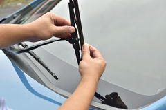 Man hand picking up windscreen wiper. Maintenance car Royalty Free Stock Images