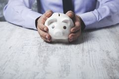Man hand piggy bank. Young business man hand holding piggy bank stock images