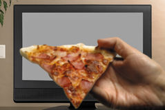 Man hand with pizza slice watching TV Royalty Free Stock Images
