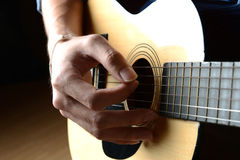 Man hand playing on acoustic guitar. Stock Photography