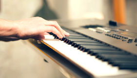 Man hand playing musical keyboard indoors Royalty Free Stock Images