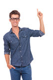 Man with hand in pocket points up. Casual young man holding a hand in his pocket and pointing upwards with the other while smiling to the camera. isolated on a Royalty Free Stock Image