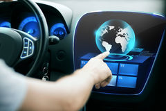 Man hand pointing finger to car monitor with globe Royalty Free Stock Images