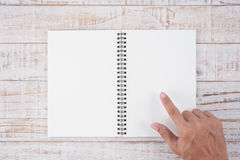 Man hand pointing notebook  on wood table for text and backgroun Royalty Free Stock Photos