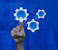 Man hand pressing gear icon with copy space over map and city ba Royalty Free Stock Photo