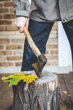 Man hand pulls ax from stump Royalty Free Stock Images