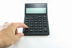 Man hand push button black calculator on white background isolated. Stock Photo