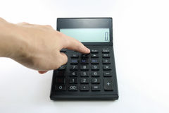 Man hand push button black calculator on white background isolated. Royalty Free Stock Images