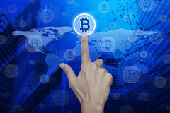 Man hand pushing bit coin icon over map and city tower, Choosing Royalty Free Stock Photography