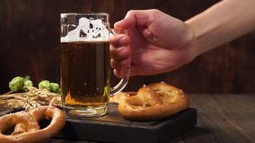 Man hand puts back a mug of light beer on a dark wooden table. Man hand puts back a mug of light beer on a dark wooden table with german pretzels stock video