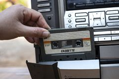 Man hand putting cassette into old fashioned audio tape player on desk wood background. Man hand putting cassette into old fashioned audio tape player on top stock photography
