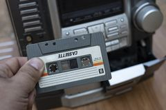 Man hand putting cassette into old fashioned audio tape player on desk wood background royalty free stock photography