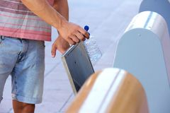 Man hand putting plastic bottle in recycling bin Stock Photography
