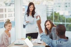 Man with hand raised while discussing with coworkers Stock Photo