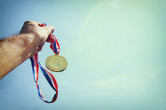 Man hand raised, holding gold medal against Sky. award and victory concept. selective focus. retro style image. Stock Photos
