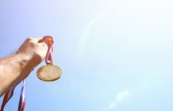 Man hand raised, holding gold medal against skyl. award and victory concept. selective focus. retro style image. Royalty Free Stock Photography
