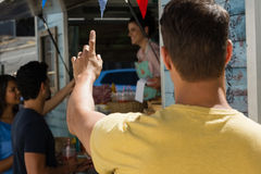 Man with hand raised standing by food truck Royalty Free Stock Photography
