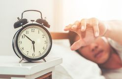Man hand reaching out to alarm clock waking up in early morning. Man hand is reaching out to alarm clock waking up in early morning stock photography