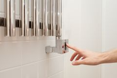 The man hand regulates thetemperature in the heated towel rail Royalty Free Stock Photography