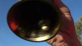 Man hand ringing brass bell on sky background stock footage