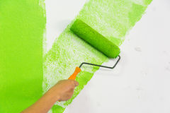Man hand with roller brush painting green color on wall Stock Images