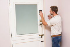 Man hand sanding the door before refinishing. At home Royalty Free Stock Photography