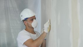 Man Hand Sanding Plaster Wall, close up.  royalty free stock photos
