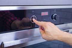 Man hand setting cooking mode on electrical oven. Male finger press button on control panel on oven, close up. Close up of man hand setting cooking mode on stock photography