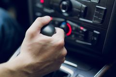 Man hand shifts gearbox in car salon. Close-up stock image