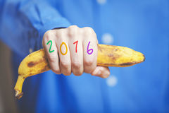 Man hand in shirt holding banana. Numbers on fingers. Man hand in a blue shirt in his hand squeezes a ripe banana. Symbol of monkey year. Figures 2016 painted royalty free stock photography