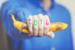 Man hand in shirt holding banana. Numbers on fingers. Man hand in a blue shirt in his hand squeezes a ripe banana. Symbol of monkey year. Figures 2016 painted royalty free stock images