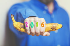 Man hand in shirt holding banana. Numbers on fingers. Man hand in a blue shirt in his hand squeezes a ripe banana. Symbol of monkey year. Figures 2016 painted stock photos