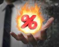 Man hand showing 3D red percentage sign with fire ball. Business man hand showing 3D red percentage sign with burning fire ball Royalty Free Stock Photography