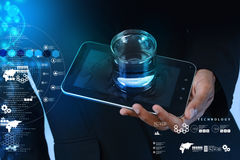 Man hand showing a glass of water and tablet phone Stock Images